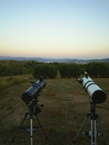 Two telescopes in a field pointing at the clear evening sky.
